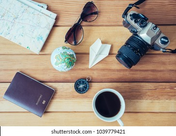 Preparation for travel,trip vacation, tourism mock up of cell phone,road map,compass,camera,sunglasses,passport,globe,coffee on wooden table.