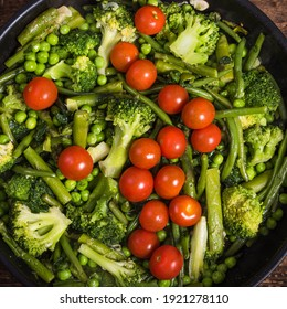 The preparation of useful vegetable dishes in a pan - broccoli, asparagus, peas and beans with tomatoes cherry in a frying pan, vegetables for cooking pasta Primavera