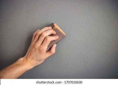 preparation of the wall before painting, hand scrubbing the gray surface with sandpaper
