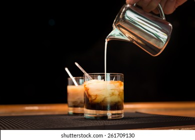 Preparation of white russian cocktails on the bar counter on rubber mat. Shallow DOF and marsala tonned