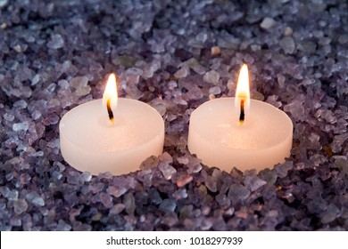 preparations for the bath and aromatherapy : two decorative candle stand in aromatic sea salt with lavender smell