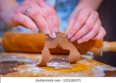 Preparations for Christmas, the hands of a woman hold a piece of cake for gingerbread cookie stars almost ready to bake