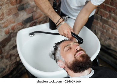 Preparations for haircut. Horizontal shot of young bearded man sitting in chair while hairdresser washing his head, close-up