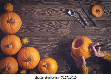 Preparations to Halloween. Hands drawing jack-o-latern on pumpkin over wooden background, top view, flat lay with copy space for text, toned image. Tools for carving lying on side