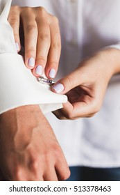 Preparations for the wedding, the bride helps the groom to wear cufflinks