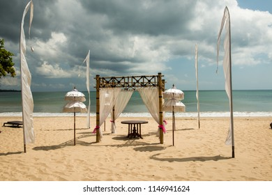 Preparations for a wedding ceremony on the beach at Jimbaran, Bali. Ominous clouds on the horizon.