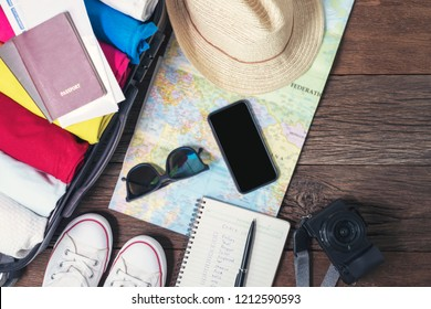 Prepare accessories and travel items, for new journey, packing clothes in suitcase bag on wooden board, flat lay, top view.
