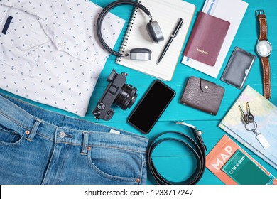 Prepare accessories and travel items, for new journey on blue wooden background, Flat lay, Top view.