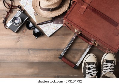 prepare accessories and travel items on brown wooden board, flat lay, top view background