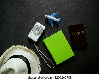 Prepare for best vocation consist of green notebook, passport, white digital compact camera and weave hat and decorated by plane model.