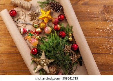 Prepare for christmas eve or other winter holidays. Xmas decorations, fir tree and garlands concept background, top view on wood. Ornaments, present packaging paper, stars, gingerbread and balls