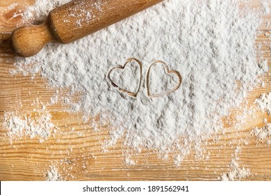Prepare cookies for the sweetest day of the year: Valentine's Day. Two hearts printed on flour scattered on a wooden table. Spread the love!