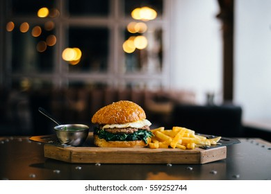 Prepare delicious fragrant golden sesame burger with fried egg spinach and meat cutlet placed on a table in wooden tray with fries golden potato and metal saucers