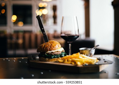 Prepare delicious fragrant golden sesame burger with fried egg spinach and meat cutlet placed on a table next to glass of red wine and fries golden potato with a knife stuck overall horizontal plan