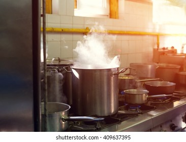 Prepare a lot of food. In a saucepan, boil the water. Cook. Restaurant kitchen. The restaurant's cuisine. Hot time. Industrial kitchen. Cooking food - process.