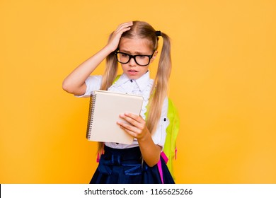 Prepare hard examen concept. Thoughtful puzzled smart clever pondering minded confused crying little girl holding textbook notebook with formula in hand touching head isolated bright background