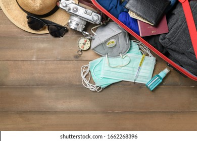 prepare hygienic mask and alcohol spray to protect against Coronavirus or COVID-19 and necessary traveler accessories on old wooden background , COVID19 virus prevention and travel concept