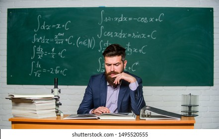 Prepare for lesson. Teacher strict serious bearded man chalkboard background. Teacher reading book. Rules of school behaviour. School principal threatening with punishment. Demanding teacher.