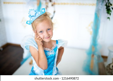 Prepare for the new year party, the snow queen or the Snow Maiden princess. Beautiful girl with a cardboard caron. Blonde holding a decoration on a wooden stick. Original accessories for photo shoots
