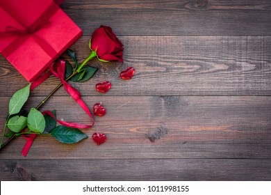 Prepare the prsesnts or surprise for Valentine's day. Red gift box near red rose on dark wooden background top view space for text
