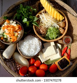 Prepare raw materials for vegan rieu noodle soup or vegetarian bun rieu, a traditional Vietnamese food with tomato, tofu, tamarind, pine apple, sausage, herbs, vegetable and rice vermicelli