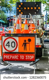 A 'Prepare To Stop' sign in front of a truck containing traffic cones and signs.