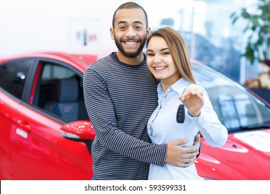 Prepare to travel! Handsome young African man embracing his beautiful girlfriend at the car dealership happy woman smiling holding car keys hugging with her handsome boyfriend interracial family love