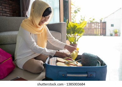 prepare for traveling. muslim asian woman put stuff on luggage