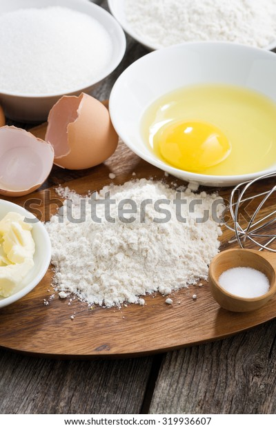 prepared baking ingredients on a wooden board, vertical, close-up