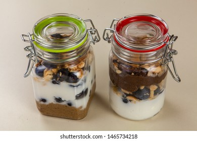 Prepared bsissa with nuts and berries. Two glass jars filled with freshly prepared bsissa, nuts, blueberries and yogurt, viewed closeup. Nourishing food preserved in airtight jars.