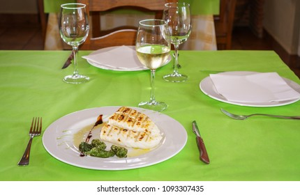 Prepared cod over plate with peppers in restaurant table
