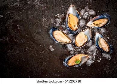 Prepared for cooking dinner seafood - fresh opened mussels on ice, on black concrete table, with lemon and seasonings. Top view, copy space