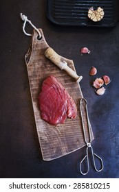 Prepared at home fresh tuna steak for grilled. Rustic image on dark table.