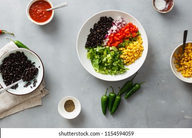 Prepared ingredients for the cooking of taco salad on gray concrete background, top view
