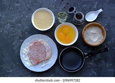 Prepared ingredients for pork chops. Meat, bread crumbs, wheat flour, eggs, salt, pepper, frying pan and frying oil
