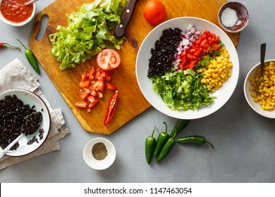 Prepared ingredients for the preparation of taco salad on gray concrete background, top view