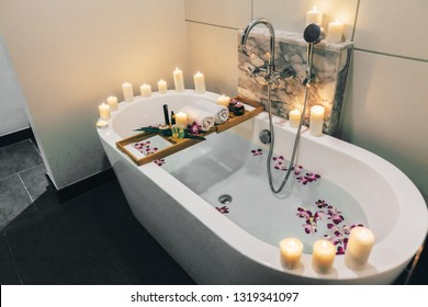 Prepared luxury spa bath decorated with flowers and candles, with wooden tray on it