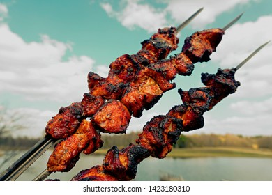 Prepared Pork shashlik on a metal skewer on blue sky with white clouds backgroun. Pork grill, Pork shashlik. Marinated shashlik preparing on a barbecue grill over charcoal. Vintage