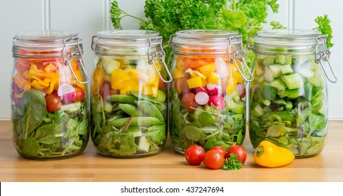 Prepared salad in glass storage jars. Four in a line on a wooden kitchen worktop. Meal prep.