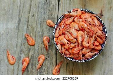 Prepared shrimp on blue plate on wooden background