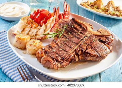 Prepared surf and turf well done steak and lobster meal with side dishes of crab cakes, shrimp and mayonnaise dip on blue wooden table