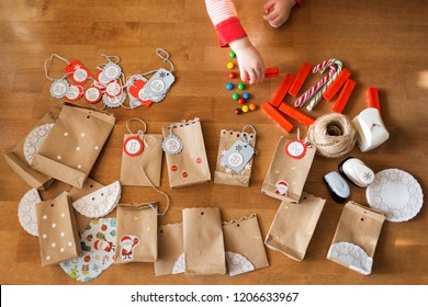 preparing the advent calendar. bags and sweets on the table. little baby arms to reach for the candy.