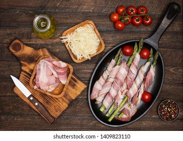 Preparing bacon wrapped asparagus on wooden table.  Cooking asparagus. Ingredients for cooking on wooden background.