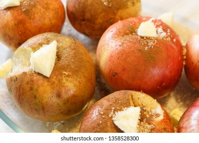 Preparing baked apples with butter, cinnamon and sugar