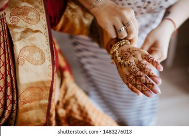 Preparing the bride for Indian wedding ceremony. The bride's hands are decorated with elaborate designs with henna tattoo.