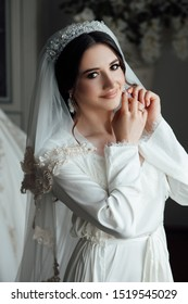 Preparing the bride for the upcoming wedding. Beautiful bride dresses earrings. Beautiful bride with stylish make up and hair style. Sexy bride. Bride's preparation at home before the wedding ceremony
