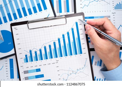 Preparing business growth plan. Business man gathering and analyzing data. Growth charts and graphs. Pile of financial reports.
