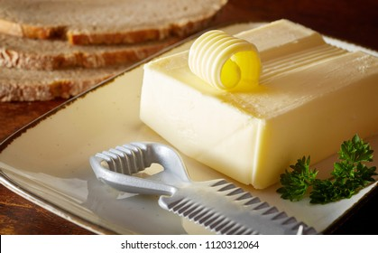 Preparing butter curls for a formal dinner with a pat of farm fresh butter on a plate with partly cut coil and metal curler alongside