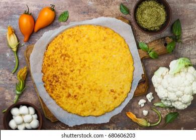 Preparing cauliflower pizza crust with pesto, yellow tomatoes, zucchini, mozzarella cheese and squash blossom.