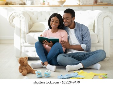 Preparing for childbirth concept. Pregnant black couple making checklist of baby things before going to maternity hospital. Loving husband taking notes of child stuff for birthing center